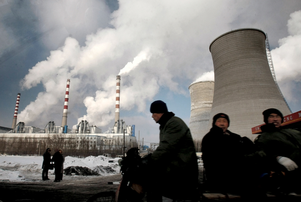 Files/The Associated Press Workers cycle past a coal-fired power plant on a tricycle cart in Changchun in northeast China's Jilin province. China's label as a developing nation in climate matters is facing a challenge. ---